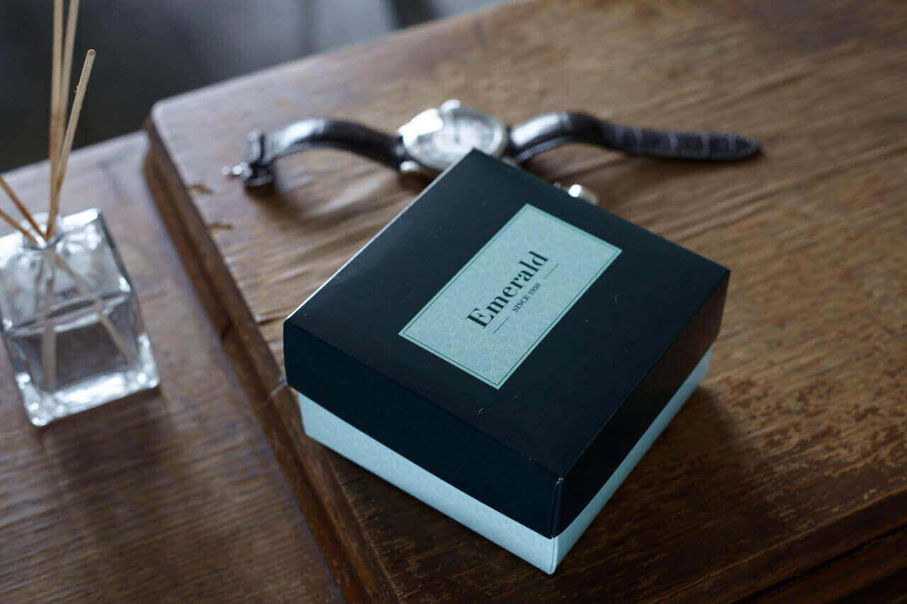 Boîte à couvercle, montre et bâtons parfumés sur une table