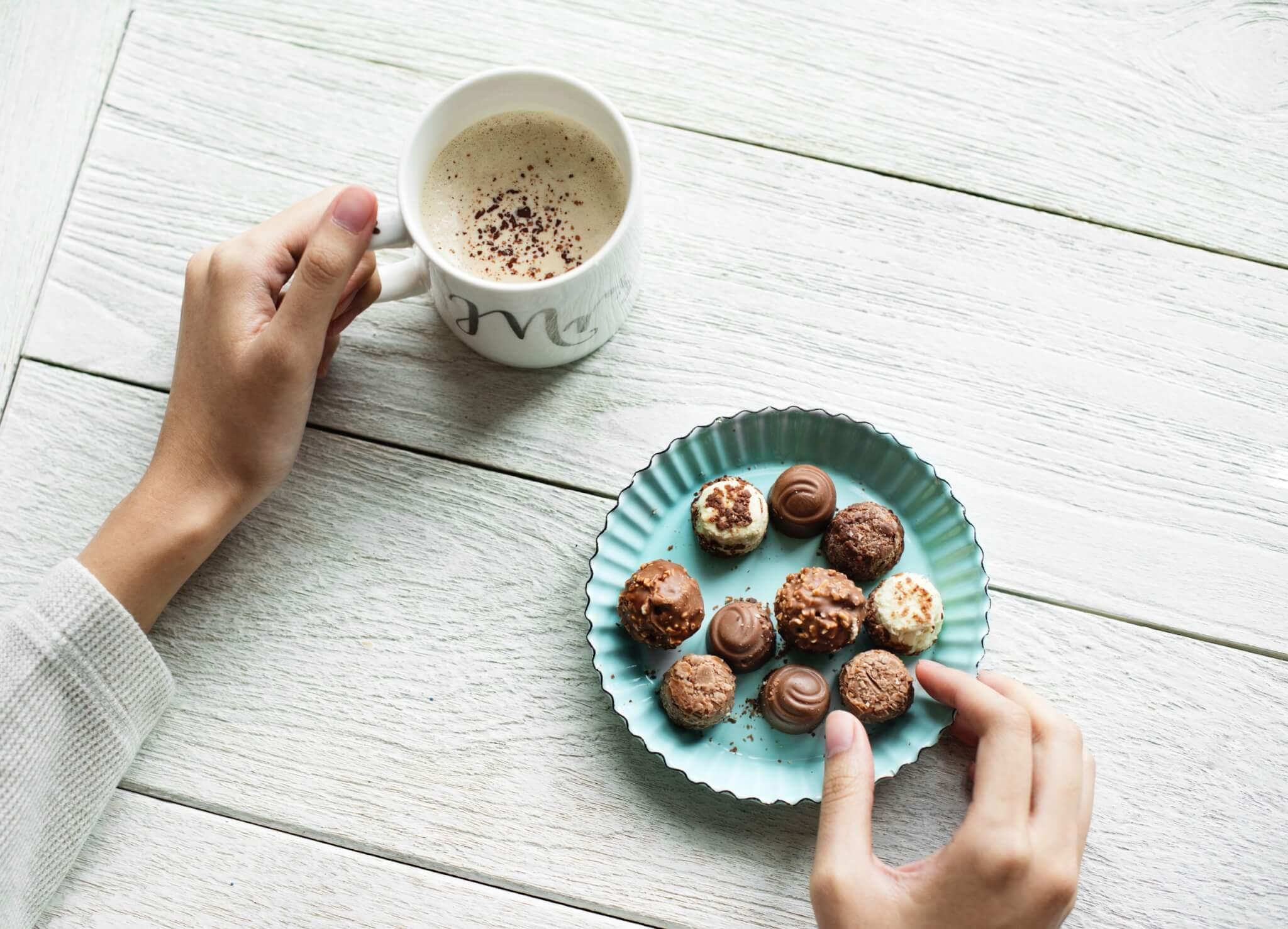 Chocolats dans une assiette et tasse de boisson chaude