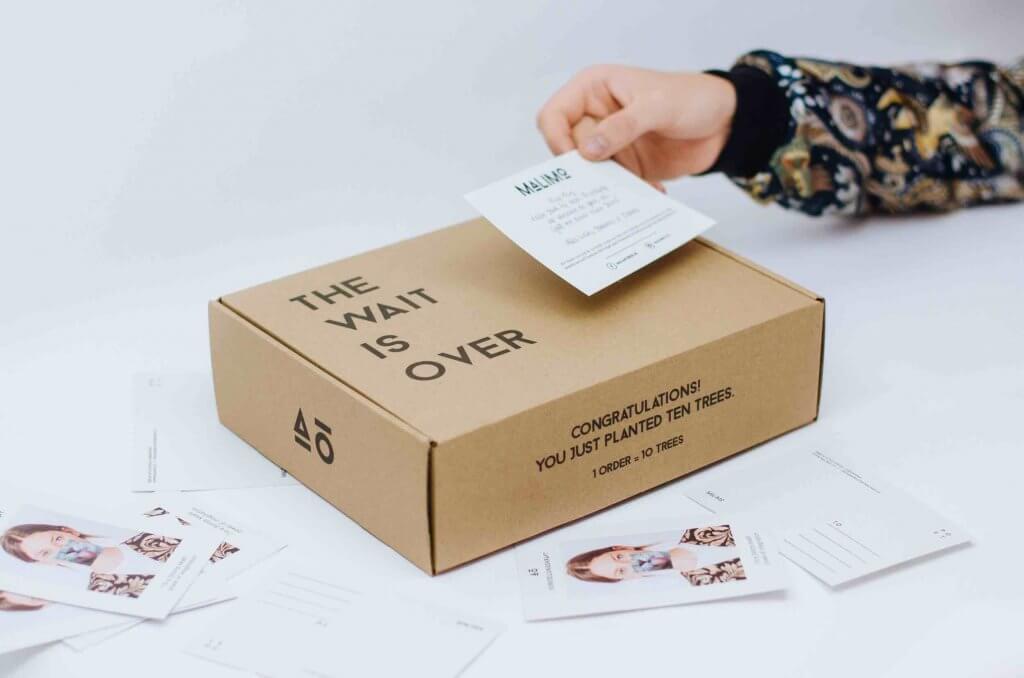 zdjęcie kartonowego pudełka z dłonią trzymającą pocztówkę