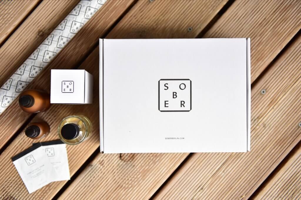 Produkte von Sober stehen neben der mit dem Logo bedruckten Verpackung - man sieht die Verpackung von Sober