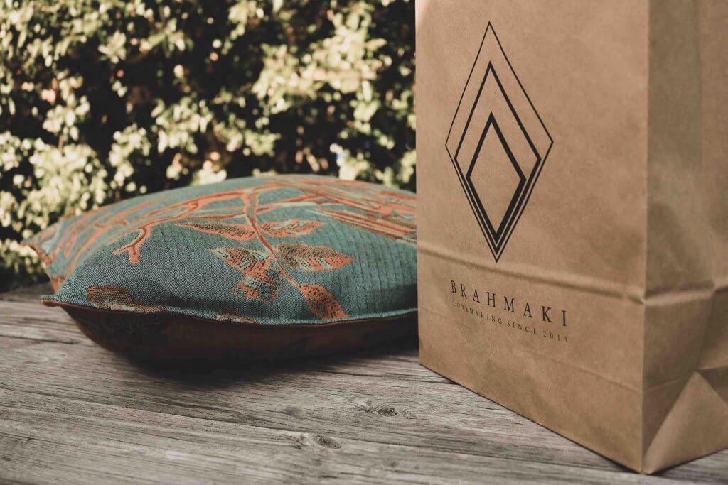 Ein Kissen von Brahmaki liegt neben einer Tüte mit logo von Brahmaki
