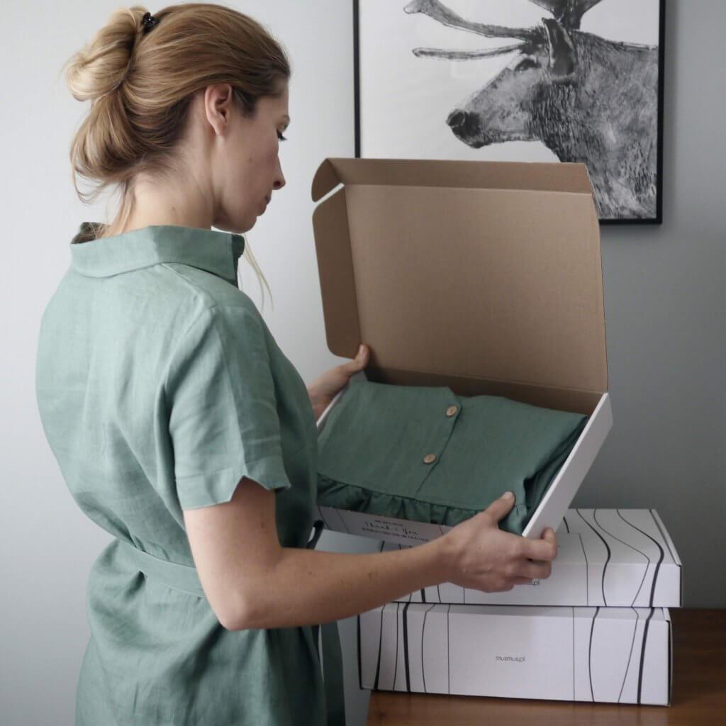 założycielka mus mus trzymająca tekturowe pudełko z nadrukiem