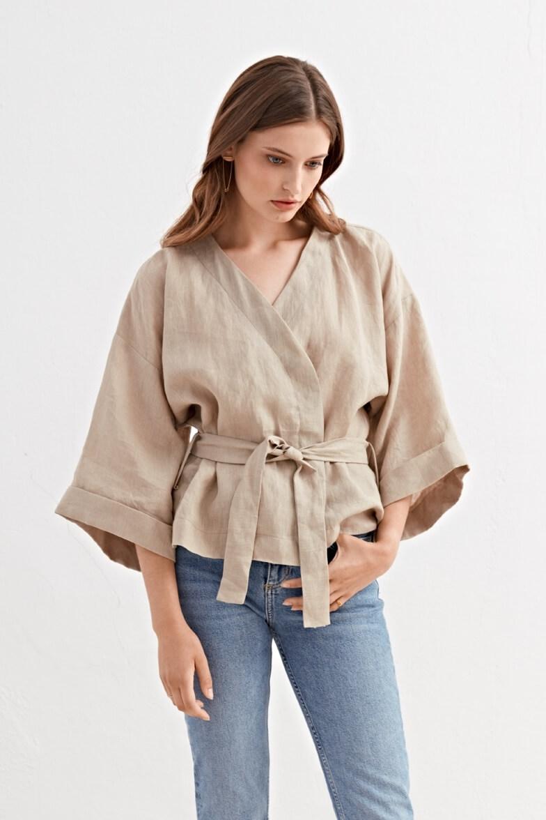 Modella con blusa sabbia e jeans su sfondo bianco