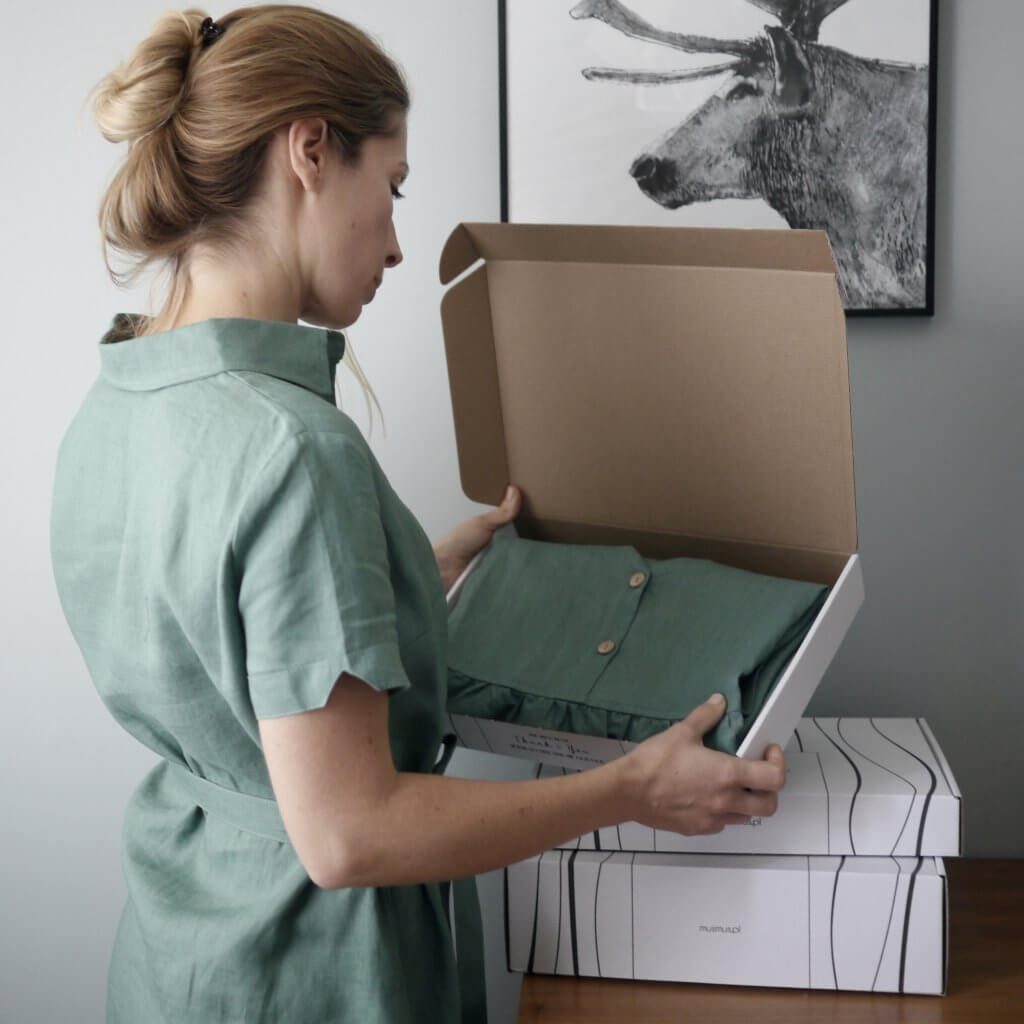 Frau schaut in eine Verpackung von Mus Mus