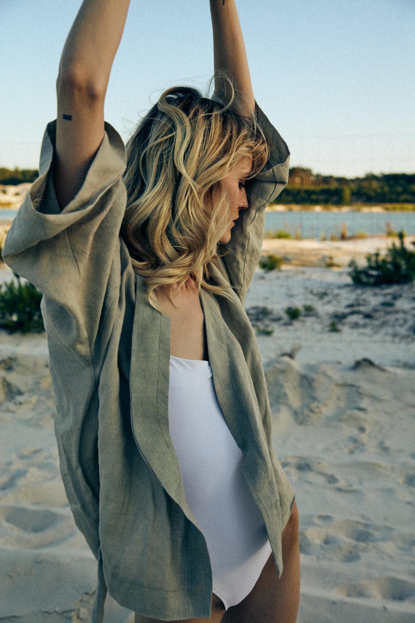 Modella con canottiera bianca e blusa color sabbia