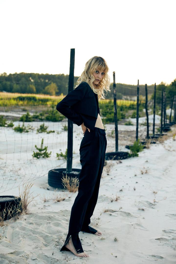 Modella con coprispalle e pantaloni neri sfondo spiaggia