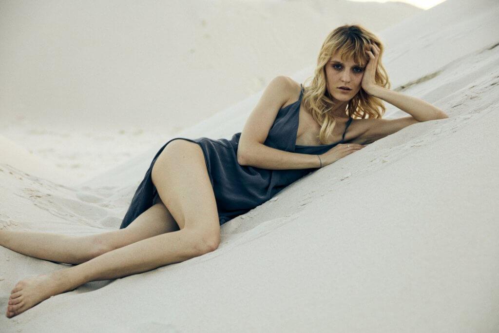 Model von Alex Ko liegt auf einer Dühne und trägt ein Kleid von Alex Ko