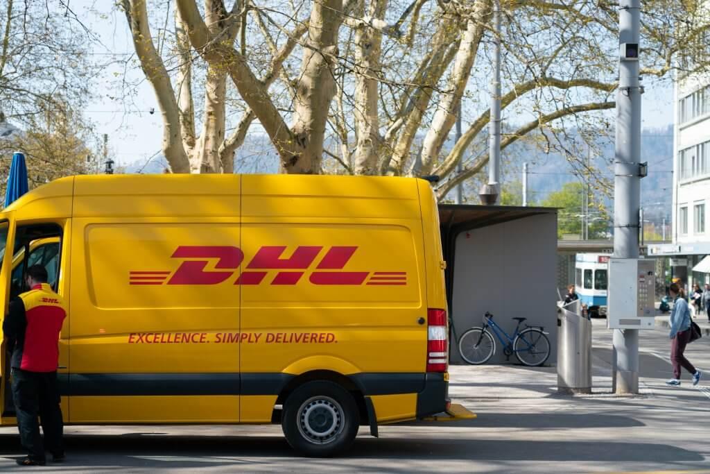 Ein Versandauto der DHL von der Seite