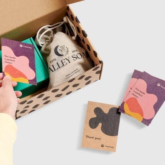 Cartes de remerciement personnalisées à côté d'un pochon en coton dans une boîte d'expédition